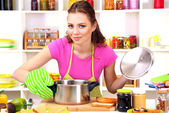 Young woman cooking in kitchen — Stok fotoğraf