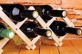 Flessen wijn geplaatst op houten voet op stenen muur achtergrond — Stockfoto