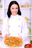 Beautiful girl chief-cooker with pizza on kitchen background — Stock Photo