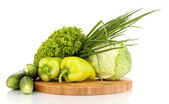 Fresh green vegetables on chopping board isolated on white — Stock Photo