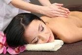 Krásná mladá žena ve spa salonu dostat masáž s wellness kameny, na tmavém pozadí — Stock fotografie