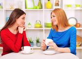 两个女孩朋友谈话和在厨房里喝的茶 — 图库照片