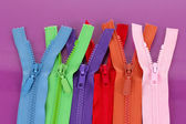 Multicolored zippers on purple background — Stock Photo