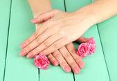 Manos de mujer con manicura rosa y flores, sobre fondo de madera de color — Foto de Stock