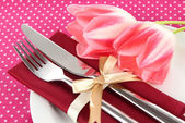 Festive dining table setting with tulips on pink polka-dot background — Stock Photo