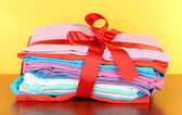 Pile of clothing with red ribbon and bow on table on yellow background — Stock Photo