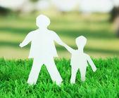 在明亮的背景上的绿色草地上纸 — 图库照片