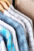 Men's shirts on hangers on wooden background — Stock Photo