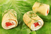 Egg rolls with cheese cream and paprika, on green salad leaves , close up — Stock Photo