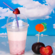Delicious milk shake with fruit on table on blue sea background — Zdjęcie stockowe