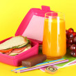 Lunch box with sandwich,grape,juice and stationery on yellow background - Stock Photo