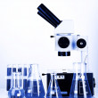 Test tubes with colorful liquids and microscope in blue light — Stock Photo