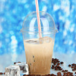 Cold coffee with ice in glass on blue background — Stockfoto