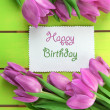 Beautiful bouquet of purple tulips and card on green wooden background — Stok fotoğraf