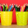 Colorful pencils in two pails on table on red background — Stock Photo #23592423