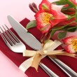 Festive dining table setting with flowers on pink background — Stock Photo #23592713