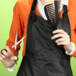 Hairdresser in uniform with working tools, on color background - Stock Photo