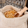 Beans in sack on wooden background - Stock fotografie