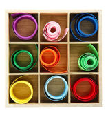 Bright silk ribbons in wooden box, isolated on white — Stock Photo