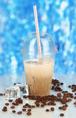 Cold coffee with ice in glass on blue background — Stok fotoğraf