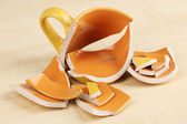 Yellow broken cup on wooden background — 图库照片