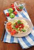 Tasty spaghetti with sauce and vegetables on plate on wooden table close-up — Stock Photo