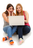 Two girl friends with with laptop isolated on white — Zdjęcie stockowe