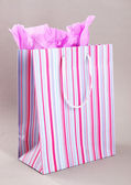 Striped shopping bag on grey background — Stock Photo
