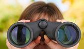 Black modern binoculars in hands on green background — Stock Photo