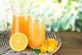 γυαλί και κανάτα χυμού πορτοκαλιού στο ξύλινο τραπέζι, σε πράσινο φόντο — Φωτογραφία Αρχείου