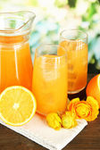 Glasses and pitcher of orange juice on wooden table, on green background — Stock Photo