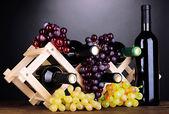 Flessen wijn geplaatst op houten voet op grijze achtergrond — Stockfoto