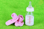 Bottle for milk and booties on towel background — Stock Photo
