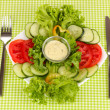 Chopped vegetables and sauce on plate on green tablecloth — Stock Photo #23601777