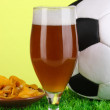 Glass of beer with soccer ball on grass on green background - Stock Photo