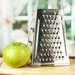 Metal grater and apple on cutting board, on bright background - Foto Stock