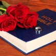 Wedding rings on bible with roses on wooden background — Stock Photo #23602769