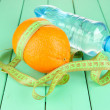 Orange with measuring tape, bottle of water, on wooden background — Stock Photo