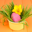 Easter egg in bowl with grass on orange wooden table close up - Foto Stock