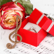 Treble clef, rose and box holding wedding ring on musical background — Stock Photo