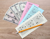 Lottery tickets with pencil and money, on wooden background — Stock Photo