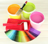 Set for painting: paint pots, brushes, paint-roller on white wooden table — Stock Photo