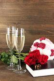 Anillos de boda en biblia con rosas y copas de champán sobre fondo de madera — Foto de Stock