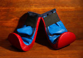 Small children boxing gloves on wooden background — Foto de Stock