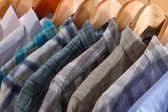 Men's shirts on hangers in wardrobe — Stockfoto