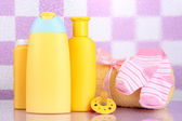 Baby cosmetics and towel in bathroom on violet tile wall background — Foto de Stock
