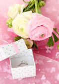Ranunculus (persian buttercups) and engagement ring, on pink cloth — Fotografia Stock