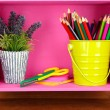 Colorful pencils in pail on shelf on wooden background — Stockfoto