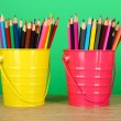 Colorful pencils in two pails on table on green background — ストック写真
