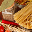 Different types of pasta, spices, tomatoes on a wooden table - Foto Stock